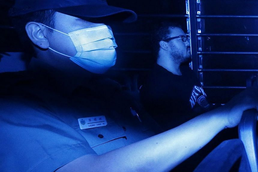 Rurik George Caton Jutting (right), a British banker charged with two counts of murder, sitting in a prison bus as he arrives at the Eastern Law Court in Hong Kong. -- PHOTO: REUTERS