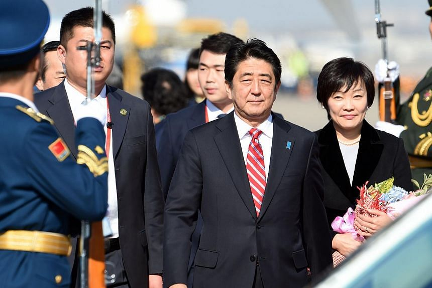 A Chinese People's Liberation Army honour guard welcomes Japan's Prime Minister Shinzo Abe and his wife Akie to the Asia-Pacific Economic Cooperation summit in Beijing on Nov 9, 2014. -- PHOTO: AFP