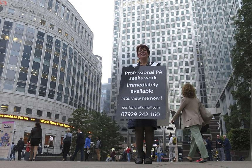 """Unemployed Gerri Spiers, who was made redundant in February 2014, standing in London's Canary Wharf financial district wearing a """"sandwich board"""" looking for employment on Sept 5, 2014. British employers plan to hire staff at the fastest rate in seve"""
