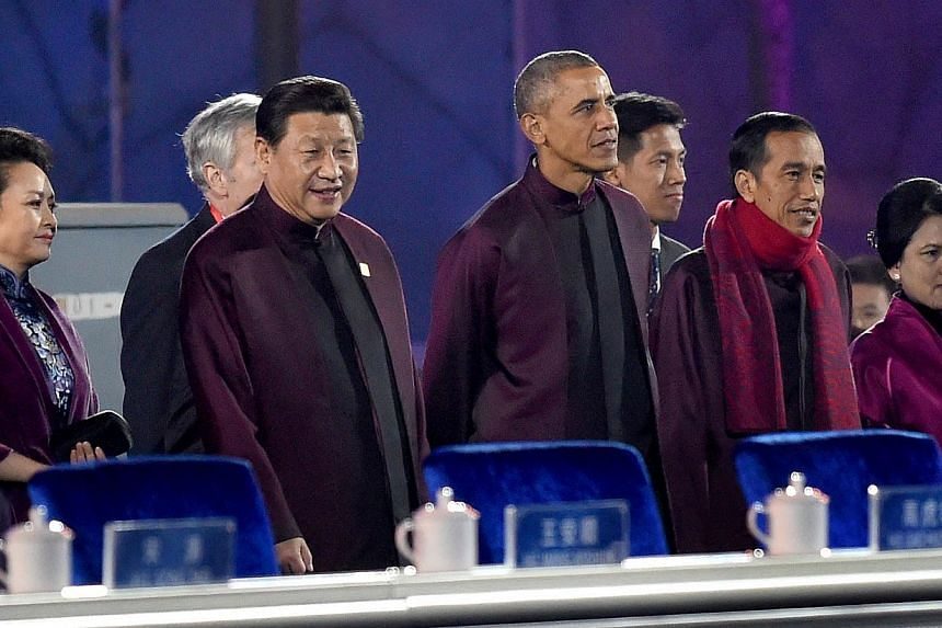 Chinese President Xi Jinping (second left) and US President Barack Obama (centre) prepare to watch the fireworks show during the Asia-Pacific Economic Cooperation (APEC) summit in Beijing on Nov 10, 2104. -- PHOTO: AFP