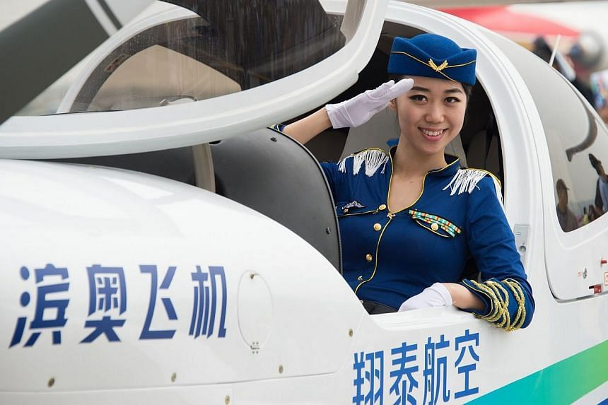 A model poses in a Binao Diamond light aircraft at the Airshow China 2014 in Zhuhai, south China's Guangdong province on Nov 11, 2014.Global aviation firms flocked to China on Tuesday to show off their wares as economic development and an expan