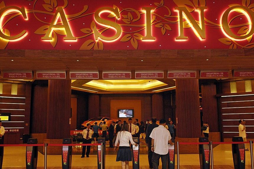 Visitors enter the casino at Genting Singapore's Resorts World Sentosa, in Singapore, May 12, 2010. -- PHOTO: BLOOMBERG