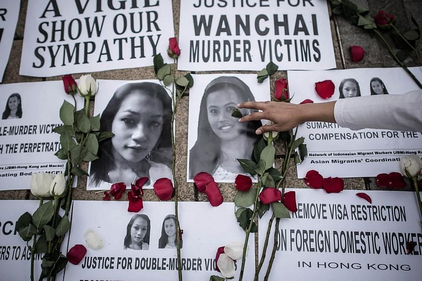 An Indonesian migrant worker lays rose pertals over the pictures of murder victims in Hong Kong on Nov 9, 2014. The bodies of Seneng Mujiasih and Sumarti Ningsih, who were allegedly murdered by a British banker in Hong Kong, have been repatriate