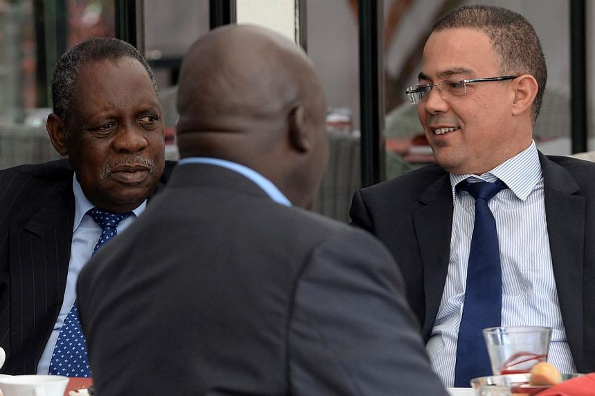 Issa Hayatou (left), Confederation of African Football (CAF) president, speaks to Fouzi Lekjaa (right), president of the Moroccan Football Federation (FRMF), during breakfast on Nov 3, 2014 in Rabat, Morocco. The north African nation was officia
