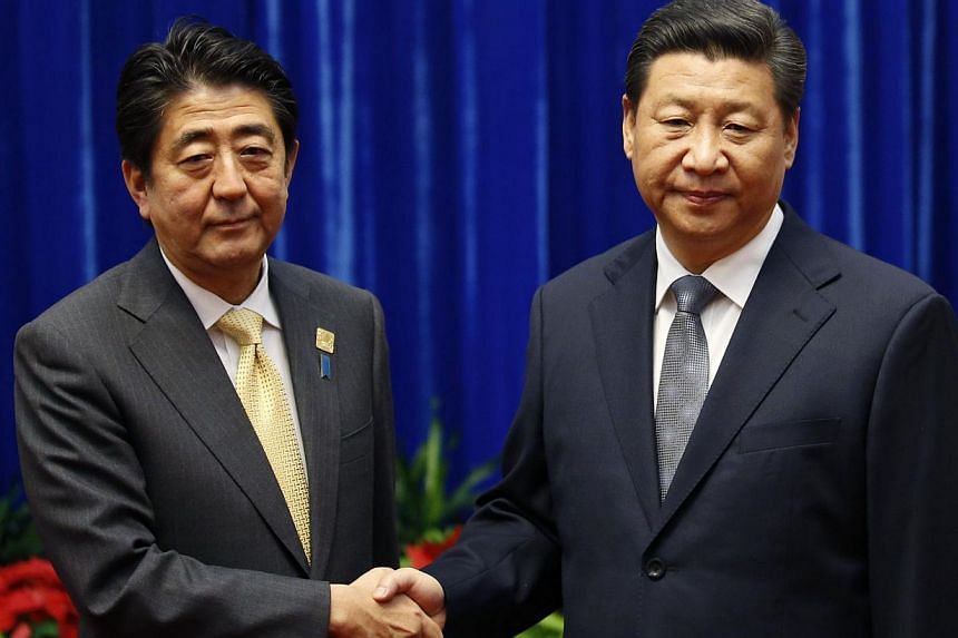 China's President Xi Jinping (right) shakes hands with Japan's Prime Minister Shinzo Abe (left) at the Great Hall of the People on the sidelines of the Asia-Pacific Economic Cooperation (APEC) Summit in Beijing on Nov 10, 2014. -- PHOTO: AFP