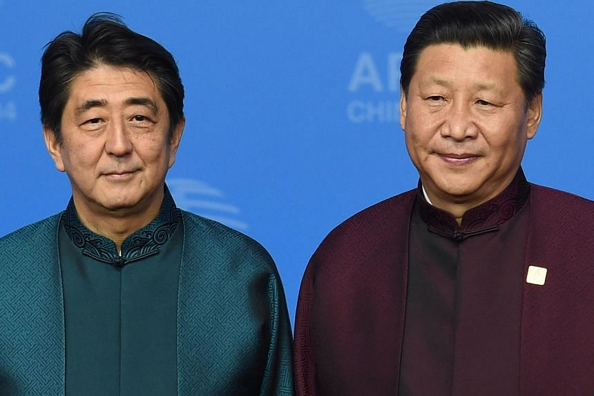 Japan's Prime Minister Shinzo Abe (left) poses with Chinese President Xi Jinping upon arrival for Asia-Pacific Economic Cooperation (APEC) Summit banquet at the Beijing National Aquatics Center in the Chinese capital on Nov 10, 2014. -- PHOTO: AFP