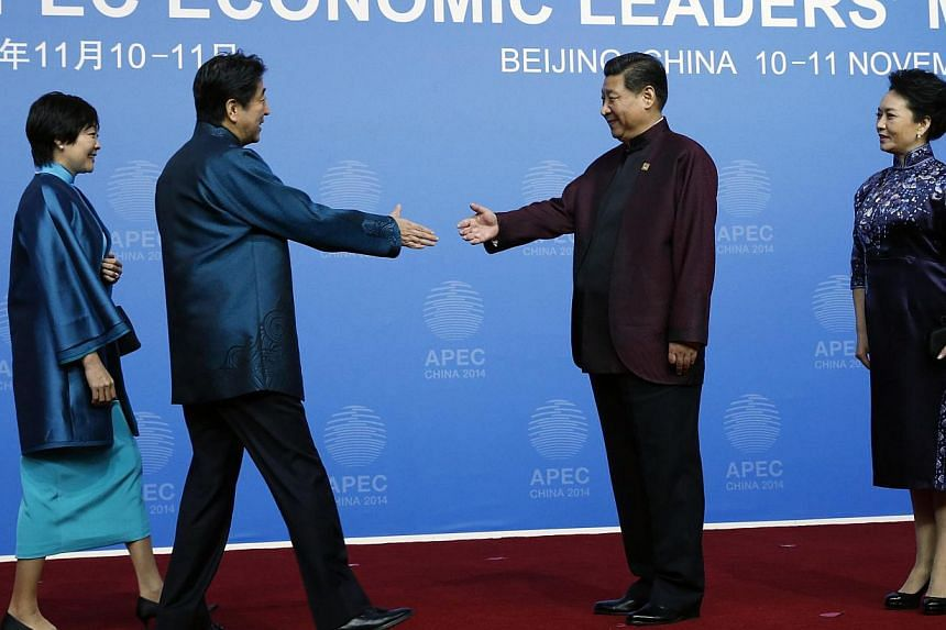Japan's Prime Minister Shinzo Abe (second left) shakes hands with China's President Xi Jinping (second right), as Abe's wife Akie (left) and Xi's wife Peng Liyuan stand beside, during the APEC Welcome Banquet at Beijing National Aquatics Center, or t