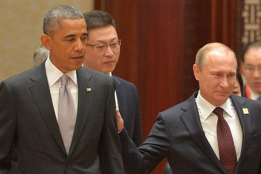 Russian President Vladimir Putin (right) and US President Barack Obama (left) at the Asia-Pacific Economic Cooperation (APEC) Summit plenary session at the International Convention Center in Beijing on Nov 11, 2014. -- PHOTO: AFP