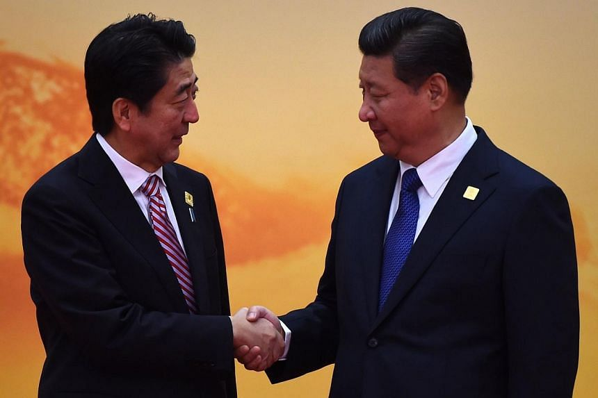 """Japan's Prime Minister Shinzo Abe (left) shakes hands with China's President Xi Jinping as he arrives for the Asia-Pacific Economic Cooperation (Apec) leaders meeting at Yanqi Lake, north of Beijing on Nov 11, 2014.China and Japan """"need each ot"""