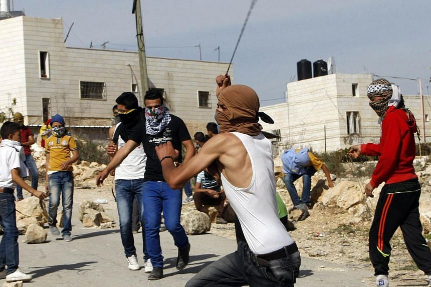 A Palestinian uses a slingshot to throw stones toward Israeli soldiers during clashes in Siear town near the West Bank city of Hebron on Nov 11, 2014. Israeli troops shot dead a Palestinian during clashes on Tuesday in the occupied West Bank, a