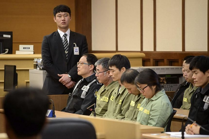 Sewol ferry captain Lee Joon Seok (man in green, wearing glasses) sits with crew members at the start of the verdict proceedings in a court room in Gwangju on Nov 11, 2014.A South Korean prosecutor said on Tuesday his team would appeal against