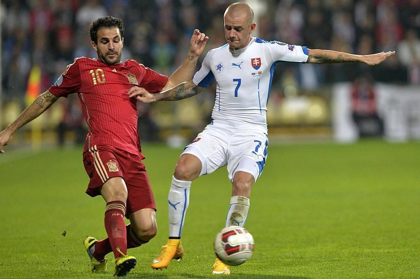 Spain's midfielder Cesc Fabregas (left) vies for the ball with Vladimir Weiss of Slovakia during the Euro 2016 qualifing football match between Slovakia and Spain in Zilina on Oct 9, 2014.Fabregas is out of Spain' Euro 2016 qualifier at home to