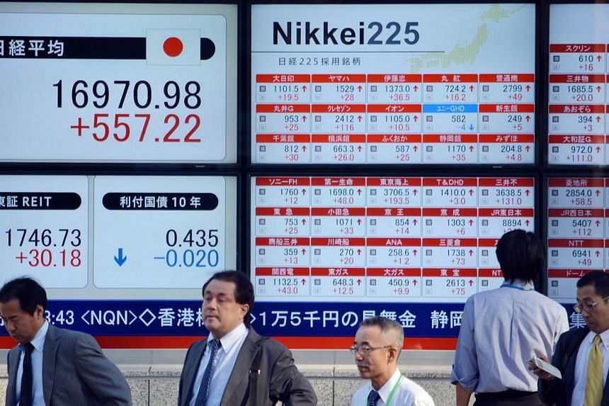 Pedestrians stand in front of stock market boards along the pavement in Tokyo on Nov 4, 2014.Japan's Nikkei share average hit a seven-year high on Tuesday as speculation swirled that Prime Minister Shinzo Abe may postpone a planned sales tax in