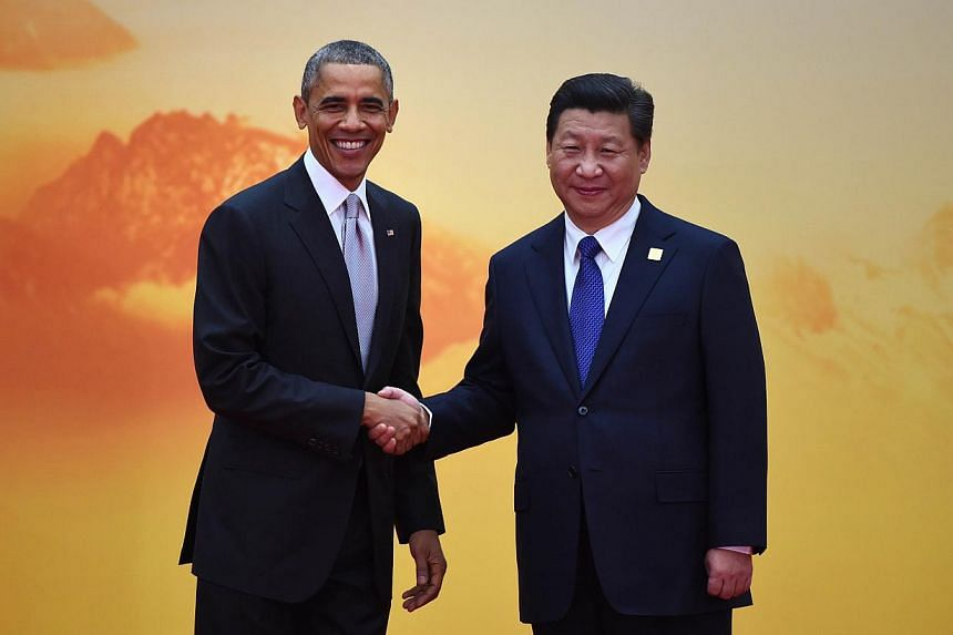 US President Barack Obama (left) shakes hands with China's President Xi Jinping as he arrives for the Asia-Pacific Economic Cooperation (Apec) leaders meeting at Yanqi Lake, north of Beijing on Nov 11, 2014. -- PHOTO: AFP