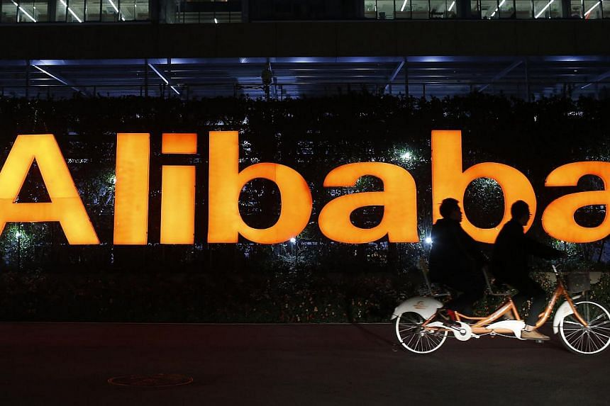 People ride a double bicycle past a logo of The Alibaba Group at the company's headquarters on the outskirts of Hangzhou, China, on Nov 10, 2014. -- PHOTO: REUTERS