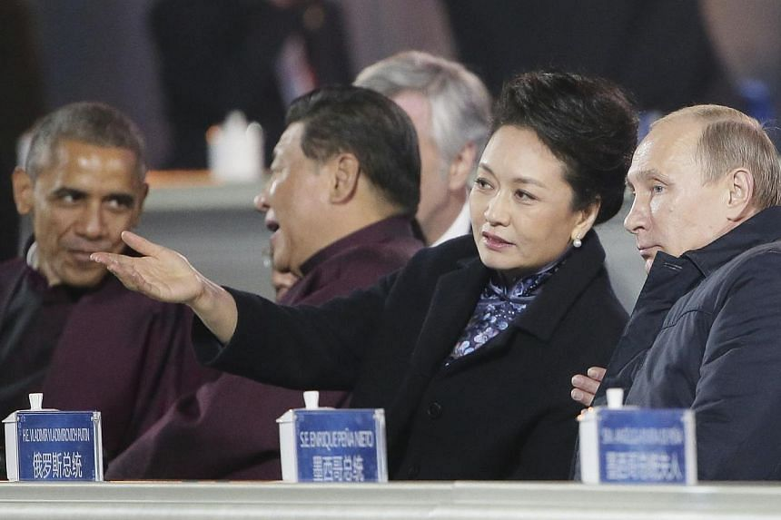 Russia's President Vladimir Putin (right), Peng Liyuan (second right), her husband Chinese President Xi Jinping (second left) and US President Barack Obama (left) watching a light show over the Beijing's Olympic Stadium during the Apec Summit. -- PHO