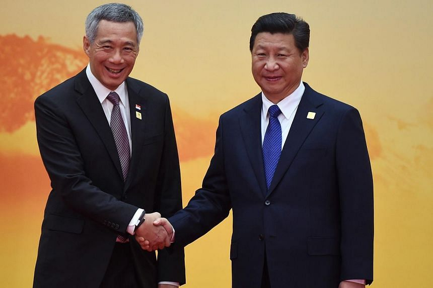 Singapore's Prime Minister Lee Hsien Loong (left) shakes hands with China's President Xi Jinping as he arrives for the Asia-Pacific Economic Cooperation leaders meeting at Yanqi Lake, north of Beijing, on Nov 11, 2014. -- PHOTO: AFP