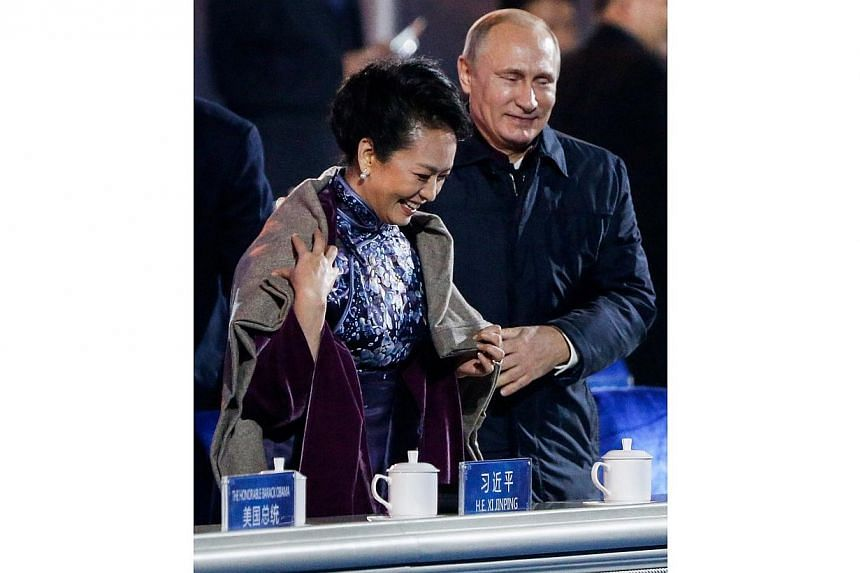 Russia's President Vladimir Putin (right) helps put a blanket on Peng Liyuan, wife of China's President Xi Jinping, as they watch a lights and fireworks show to celebrate Asia-Pacific Economic Cooperation (APEC) Leaders' Meeting, at National Aquatics