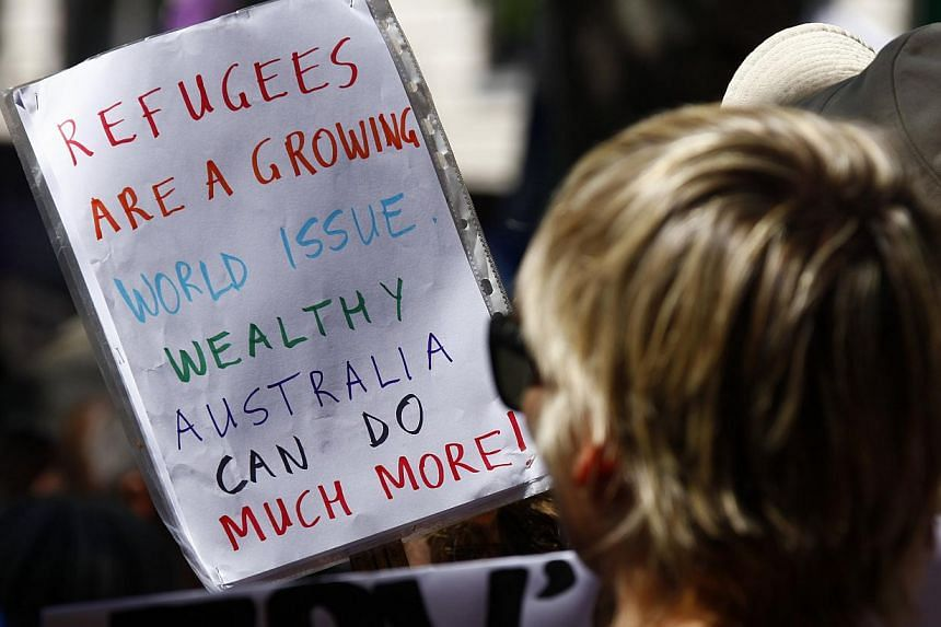Protesters hold placards at the 'Stand up for Refugees' rally held in central Sydney on Oct 11, 2014. Around a thousand protesters attended the rally, demanding changes to the Australian government's current policies for refugees. -- PHOTO: REUTERS