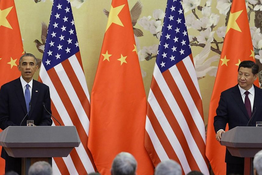 U.S. President Barack Obama (left) speaks to the media in front of U.S. and Chinese national flags during a joint news conference with China's President Xi Jinping (right) at the Great Hall of the People in Beijing on Nov 12, 2014. -- PHOTO: REUTERS&