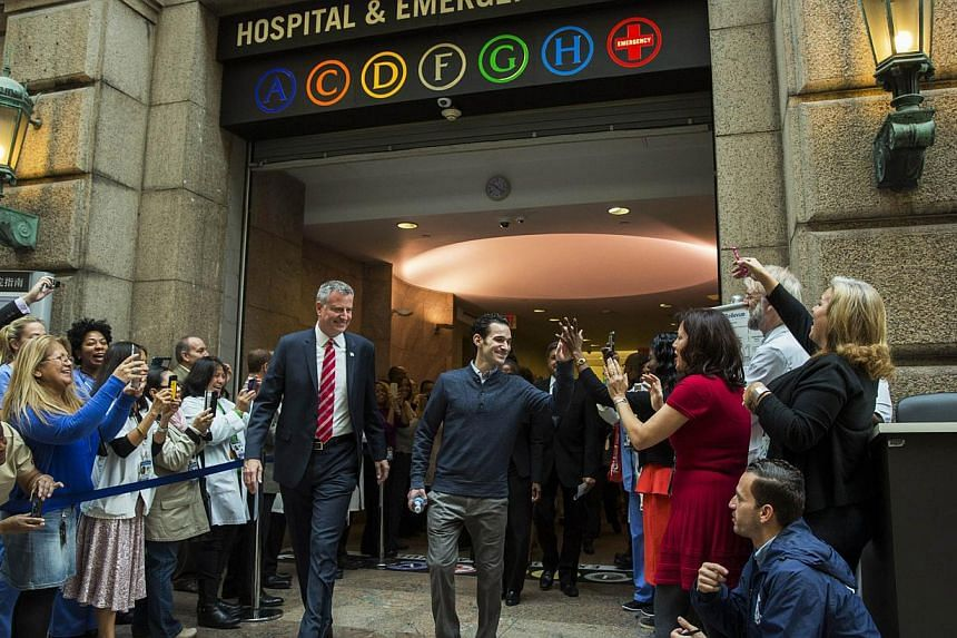 New York Mayor Bill de Blasio walks with Dr. Craig Spencer (centre) as he is discharged from Bellevue Hospital, after being declared free of the Ebola virus, in New York Nov 11, 2014. -- PHOTO: REUTERS
