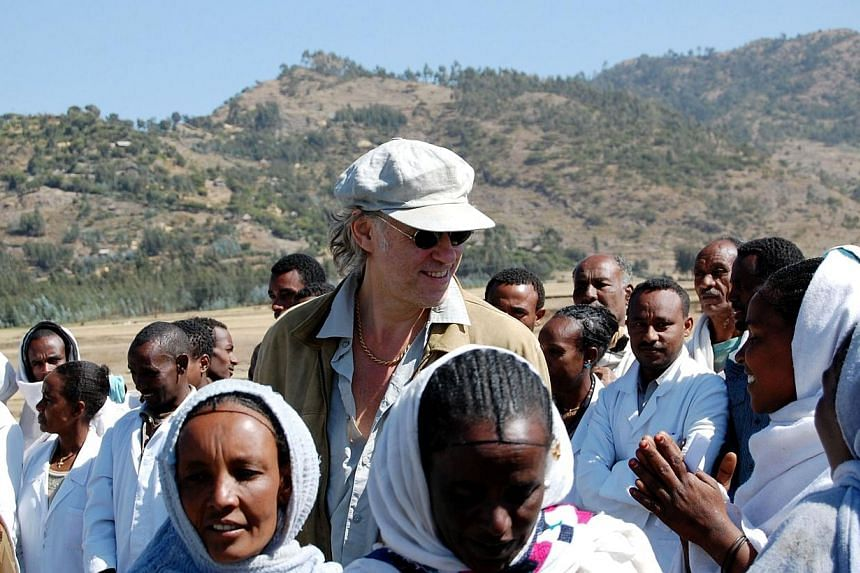 Irish founder of the Band-aid charity Bob Geldof (centre) with local people during a visit to Korem in Ethiopiaon Nov 25, 2009.A new group of stars coming together to record a new version of Do They Know It's Christmas this year to raise
