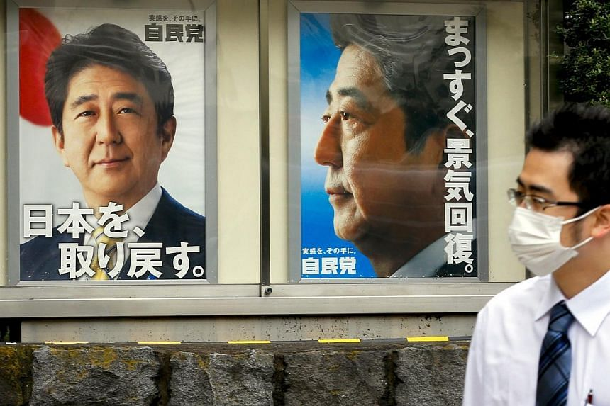 A man walks past posters of Japanese Prime Minister Shinzo Abe outside the headquarters of his Liberal Democratic Party (LDP) in Tokyo on Nov 12, 2014. MrAbe could call a snap election for next month, two years early, with a plan to boost his s