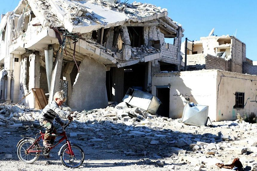 A Syrian boy rides his bike past a destroyed building in the northern Syrian city of Aleppo on Nov 5, 2014. -- PHOTO: AFP
