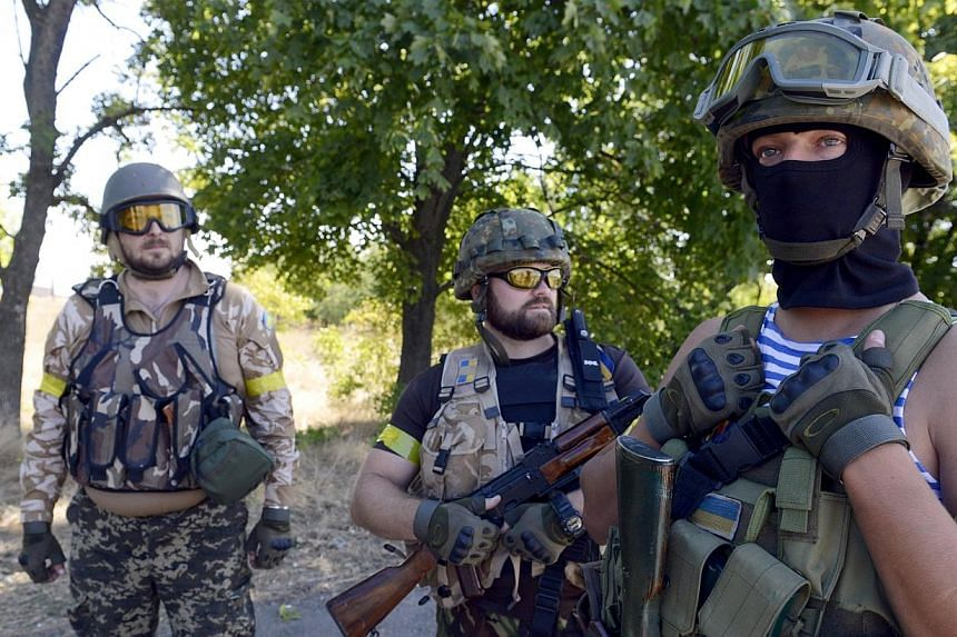 Members of Ukrainian volunteer battalion Dnipro stand as they patrol near the small southern Ukrainian city of Novoazovsk, Donetsk region on Aug 27, 2014. Ukraine said on Wednesday it was readying for fresh combat operations in the war-torn east