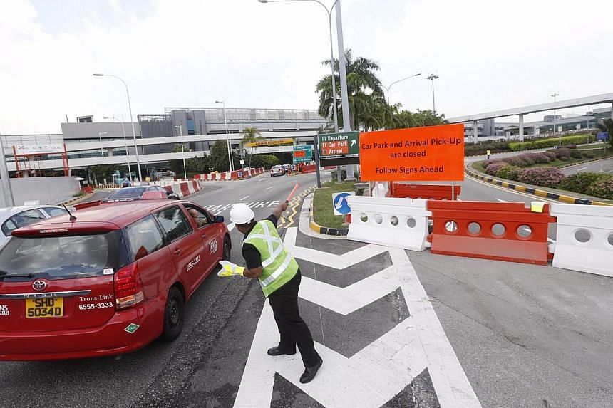 A marshall directing traffic to the new carpark as well as the new T1 arrival pick-up at the closed road of the old T1 carpark on November 12, 2014.-- ST PHOTO: KEVIN LIM
