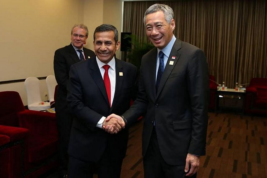 PM Lee shakes hands with Peruvian President Ollanta Humala at the 2014 Apec economic leaders' meeting in a picture posted on PM Lee's Facebook page on Nov 12, 2014. -- PHOTO: FACEBOOK OF LEE HSIEN LOONG