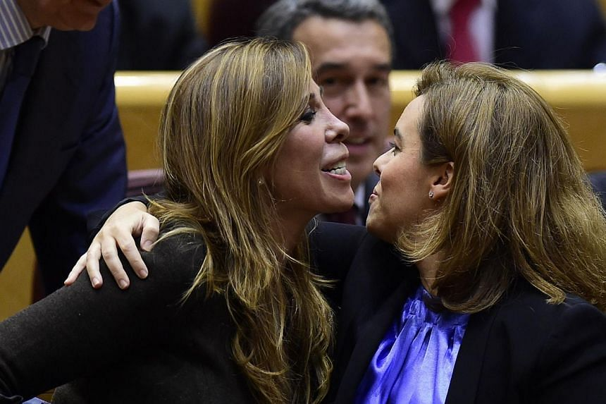 """Vice-President of the Government Soraya Saenz de Santamaria (right) kisses president of the Popular Party in Catalonia Alicia Sanchez Camacho at the senate in Madrid on Nov 11, 2014. Spain's government said today it was """"not possible"""" to grant the Ca"""