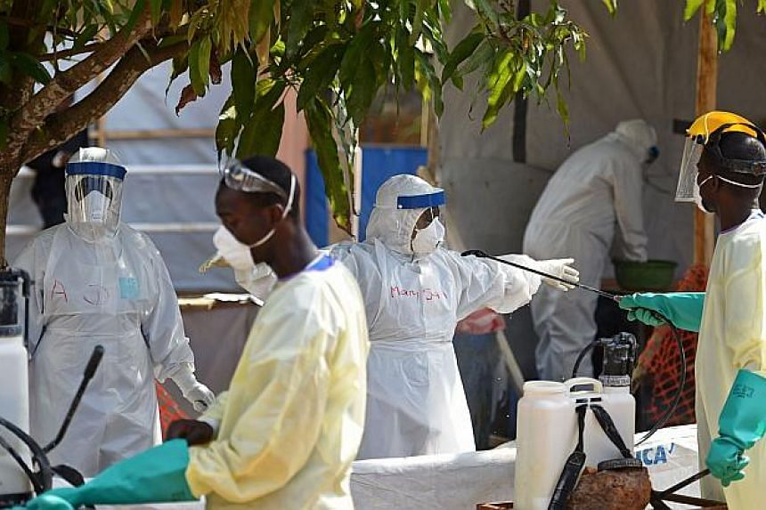 Health workers get sprayed with disinfectant on Nov 11, 2014 in the red zone of the Hastings treatment centre in Hastings, outside Freetown. Sierra Leone will make a one-off payment of US$5,000 (S$6,400) to the family of any health worker who di