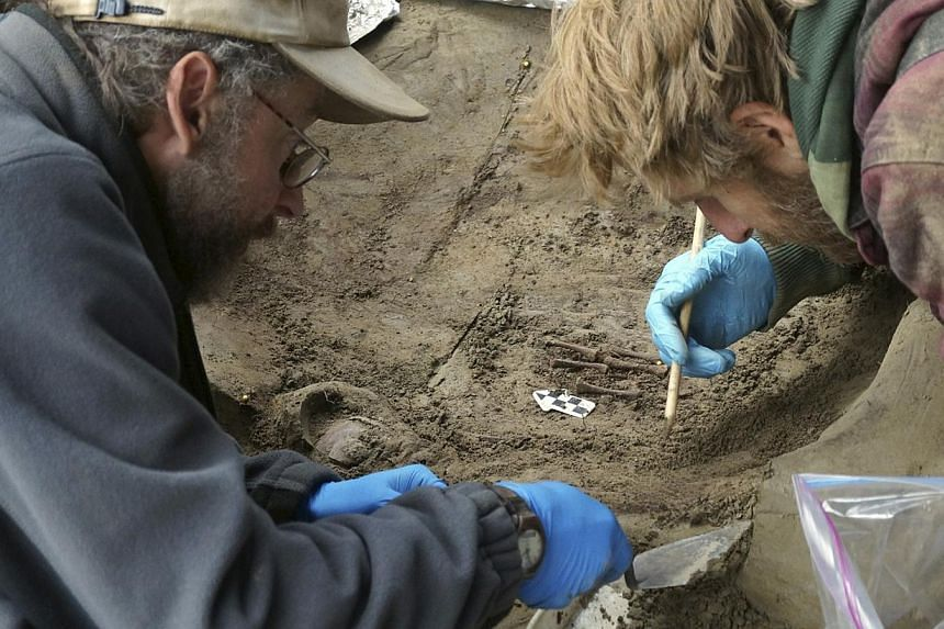 University of Alaska Fairbanks (UAF) professors Ben Potter (left) and Josh Reuther excavate the burial pit at the Upward Sun River site in central Alaska in this undated handout photo provided courtesy of Ben Potter, on Nov 11, 2014.  -- PHOTO: