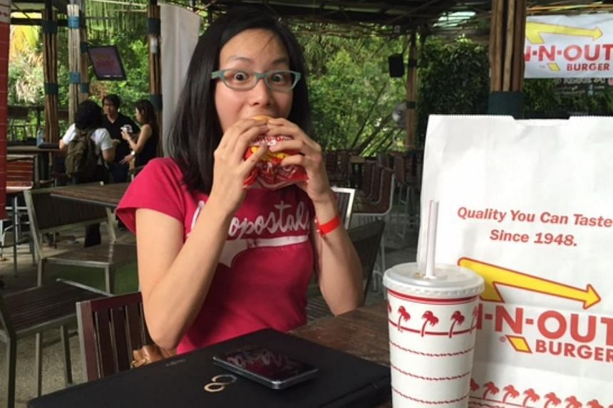 Student Alicia Lim, 19, enjoying her double-double burger. -- ST PHOTO: AUDREY TAN