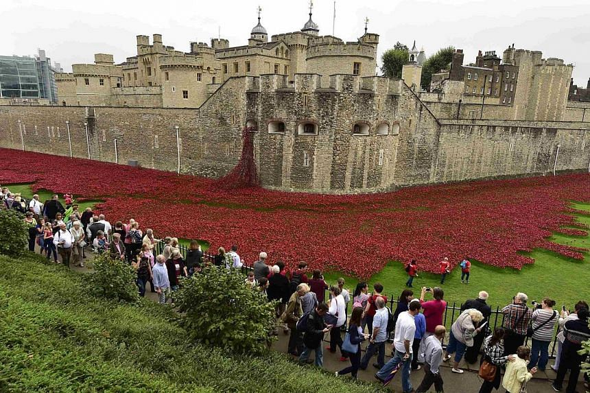 Tourists watch as volunteers plant ceramic poppies for the art installation called Blood Swept Lands And Seas Of Red at the Tower of London Sept 20, 2014.A teenage army cadet on Tuesday planted the last of 888,246 ceramic poppies at the Tower o