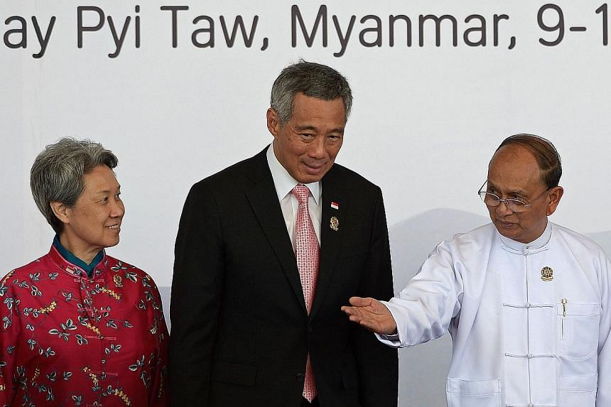 Myanmar President Thein Sein (right) welcomes Singapore's Prime Minister Lee Hsien Loong (centre) and his wife Ho Ching ahead of the 25th Asean Summit at the Myanmar International Convention Centre in Myanmar's capital Naypyidaw on Nov 12, 2014. -- P