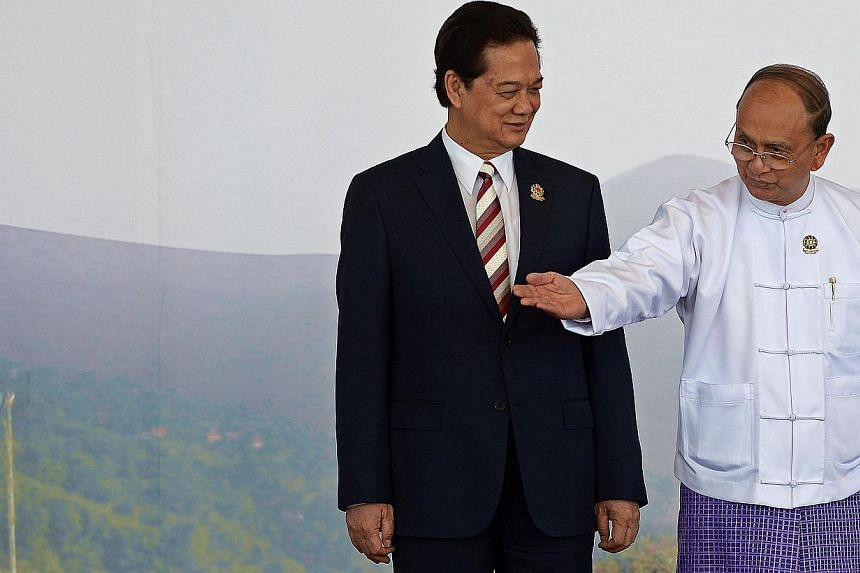 Myanmar President Thein Sein (right) gestures after welcoming Vietnam's Prime Minister Nguyen Tan Dung ahead of the 25th Asean Summit at the Myanmar International Convention Centre in Myanmar's capital Naypyidaw on Nov 12, 2014. -- PHOTO: AFP