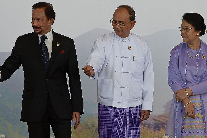 Myanmar President Thein Sein (centre) and his wife Khin Khin Win (right) welcome Brunei's Sultan Hassanal Bolkiah ahead of the 25th Asean Summit at the Myanmar International Convention Centre in Myanmar's capital Naypyidaw on Nov 12, 2014. -- PHOTO: