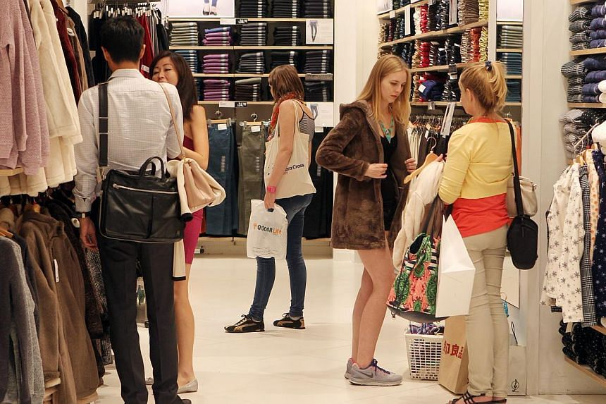 Shoppers browsing at clothes in fast fashion store Uniqlo at ION Orchard. -- PHOTO: ST FILE