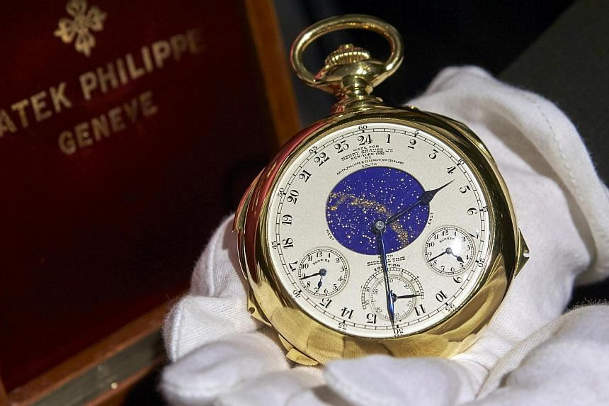 """A staff member holds """"The Henry Graves Supercomplication"""" handmade watch by Patek Philippe at Sotheby's auction house in Geneva Nov 5, 2014. The timepiecefetched a record US$21.3 million (S$27.5 million) when it went under the hammer in Switzer"""