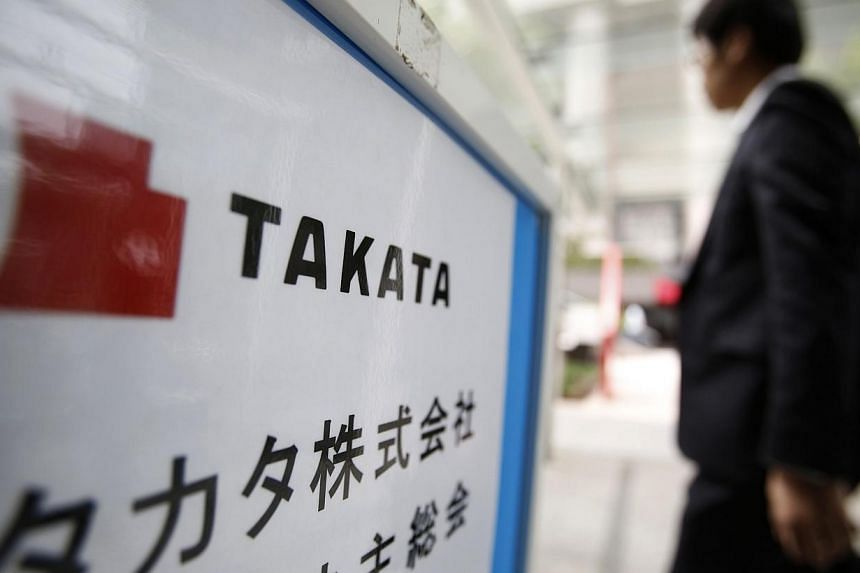 A man walks past a sign board of Japanese auto parts maker Takata Corp's Annual General Meeting in Tokyo in this June 26, 2014 file photograph. Japanese auto parts maker Takata on Thursday rejected a high-profile report that claimed it had cover
