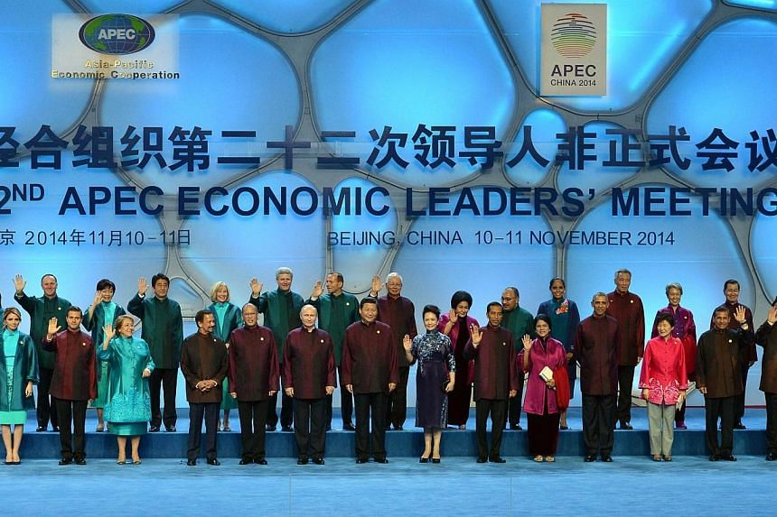 "This file photo taken on Nov 10, 2014 shows leaders and their spouses of the Asia-Pacific Economic Cooperation (Apec) economies posing for a ""family photo"" at the Beijing National Aquatics Center in the Chinese capital. Chinese traders are offer"