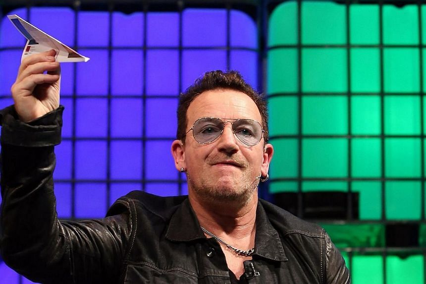U2 frontman Bono throws a paper aeroplane back into the audience as he speaks on centre stage during the last day of the Web Summit in Dublin, Ireland, on Nov 6, 2014.A private plane carrying U2 frontman Bono lost its rear hatch while approachi