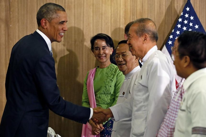 Myanmar opposition leader Aung San Suu Kyi looks on as U.S. President Barack Obama shakes hands after a roundtable with members of parliament and civil society to discuss Myanmar's reform process in Naypyitaw, Myanmar on Nov 13, 2014.US Preside