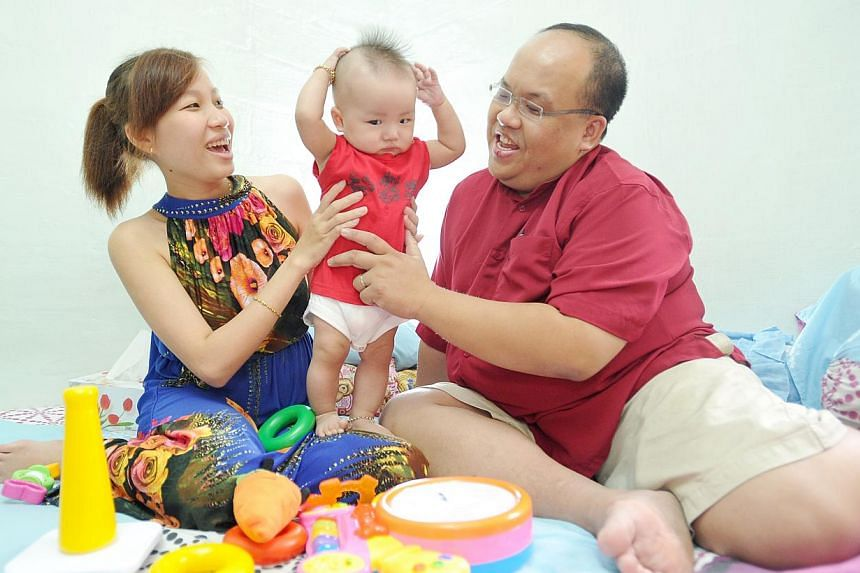 Dennis Ng and his wife Nguyen Thi Dieu Hien with their son Jayden Ng, seven months, at their house on Jul 16, 2013. More than 13,000 fathers have used paid paternity leave since the benefit was introduced in May last year as part of the enhanced Marr