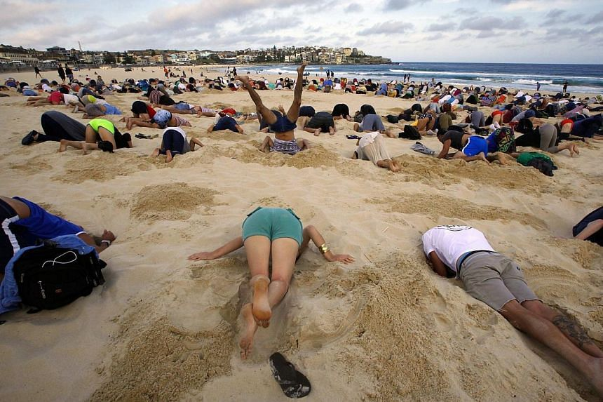 A group of around 400 demonstrators participate in a protest by burying their heads in the sand at Sydney's Bondi Beach on Nov 13, 2014. Scores of Australians buried their heads in the sands of iconic Bondi Beach on Thursday to send a mess