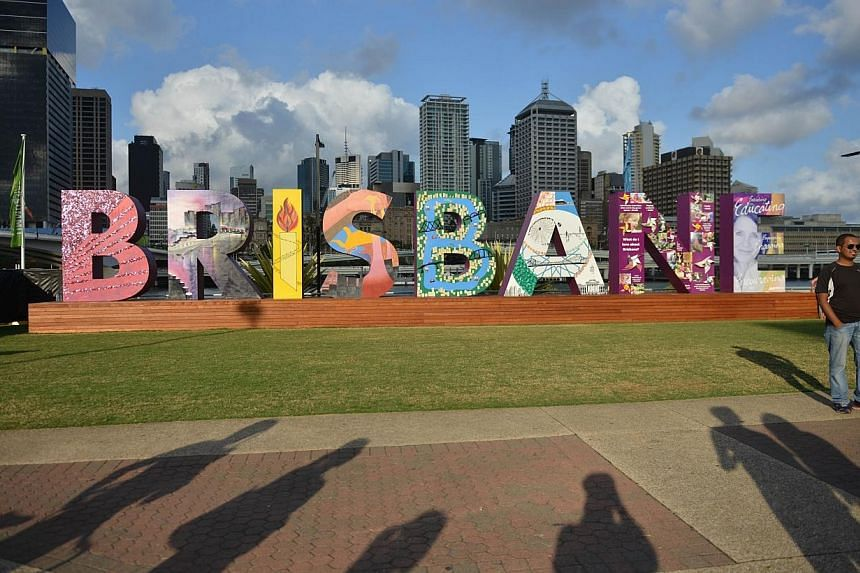 "A visitor poses for photos in front of a ""Brisbane"" artwork along the Brisbane River bank on Nov 13, 2014, ahead of the G20 Summit.  Prime Minister Lee Hsien Loong will be in Brisbane, Australia, on Saturday and Sunday for the Group of 20 ("