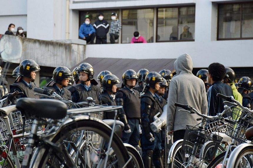 Fully clad riot police raid a dormitory at the Kyoto University in Kyoto, western Japan on Nov 13, 2014 as plain clothed police search the domitory, in an apparently heavy-handed response to a left-wing movement that may involve students.Scores