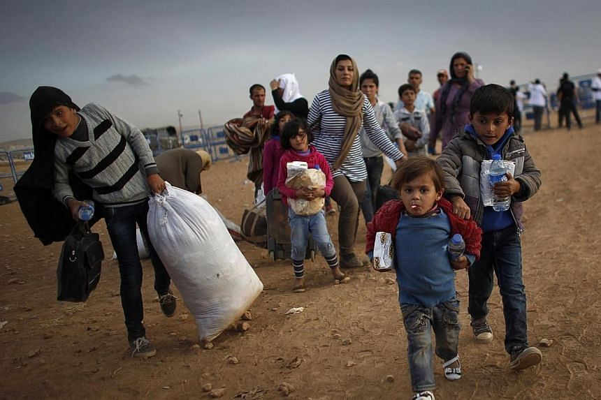 Kurdish Syrian refugees carry their belongings after crossing the Turkish-Syrian border near the southeastern town of Suruc in Sanliurfa province on Sept 25, 2014.Turkey is to issue work permits for some of the 1.5 million Syrian war refugees i